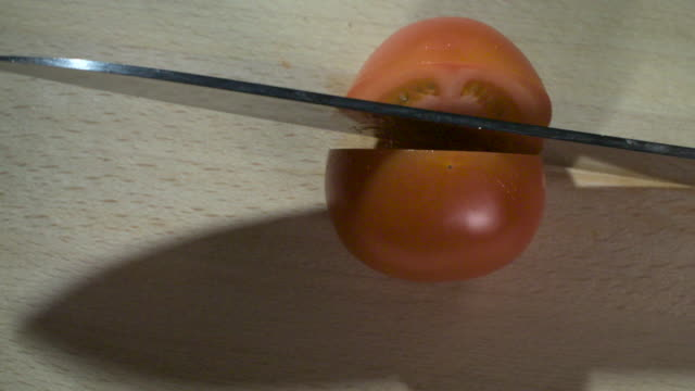Slow motion shot of a kitchen knife cutting a tomato in half.
