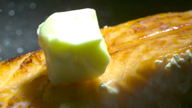 Slow motion shot of a knob of butter falling onto a cooked salmon steak.