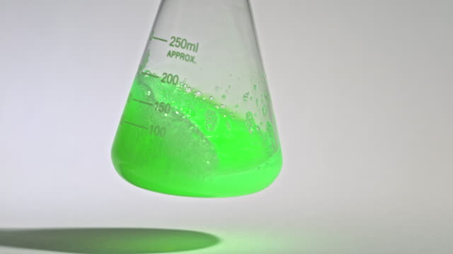 slow motion shot of a liquid being swirled in a laboratory flask, turning from green to yellow. - laboratory flask stock videos & royalty-free footage