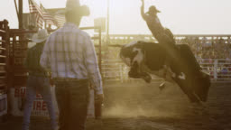 Slow Motion Shot of a Male Bull Rider Competing in a Bull Riding Event in a Stadium Full of People at Sunset