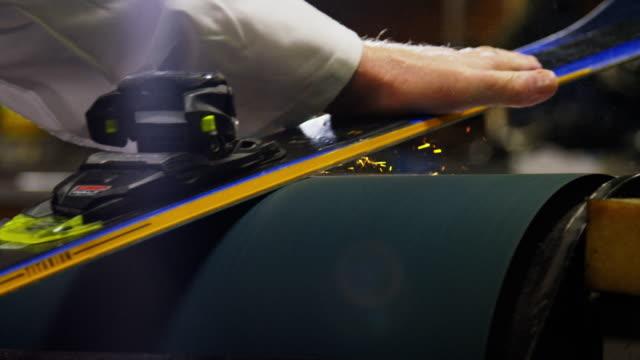 vídeos de stock, filmes e b-roll de tiro de câmera lenta de um técnico de esqui caucasiano masculino em seus cinquenta usando um moedor de cinto para suavizar o fundo de um esqui downhill como faíscas voam em uma loja de reparos interiores - equipamento esportivo