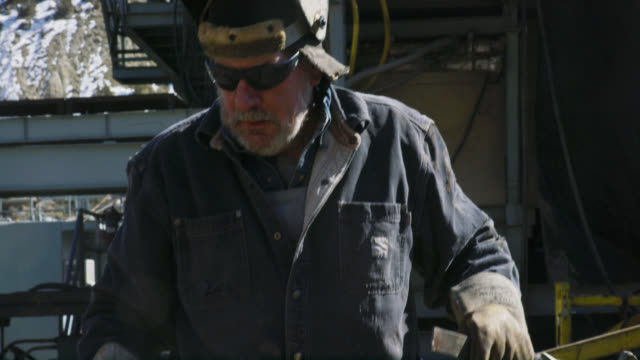 slow motion shot of a male oilfield worker in his sixties wearing a welding mask carries a hammer and a file next to a derrick at an oil and gas drilling pad site on a sunny day - hammer stock videos & royalty-free footage