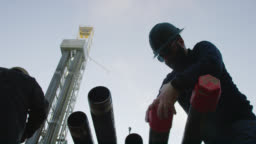 Slow Motion Shot of a Male Oilfield Worker Putting on a Drilling Pipe Thread Protector Cap with a Derrick Behind Him at an Oil and Gas Drilling Pad Site