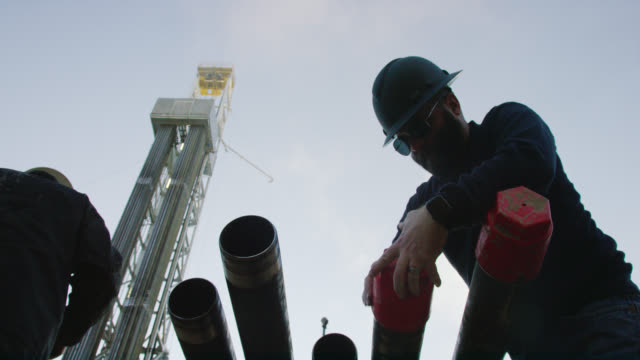 slow motion shot of a male oilfield worker putting on a drilling pipe thread protector cap with a derrick behind him at an oil and gas drilling pad site - career stock videos & royalty-free footage