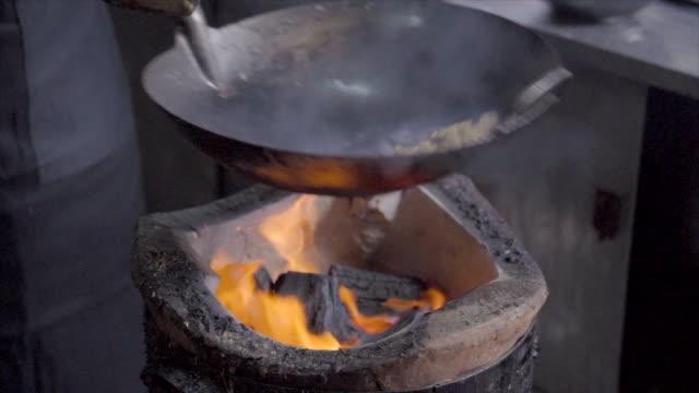 vídeos de stock, filmes e b-roll de tiro de movimento lento de um homem que cozinha com fogão de carvão. prato de macarrão na frigideira em fogo aberto. comida de rua em chinatown de bangkok, tailândia - fogão
