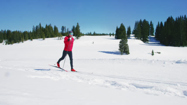 slow motion shot av en man i femtioårsåldern längdskidåkning i bergen på en solig, vinterdag i colorado - längd bildbanksvideor och videomaterial från bakom kulisserna