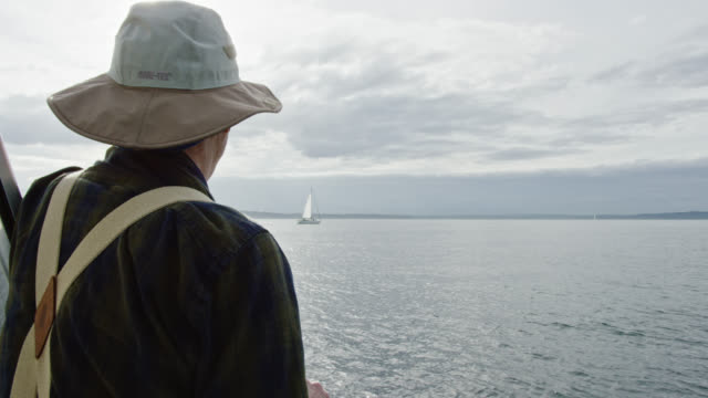 slow motion shot of a man in his sixties looking out over puget sound in washington from the deck of a sailboat on a partly cloudy day - mast sailing stock videos & royalty-free footage