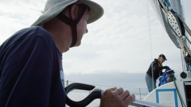 vídeos de stock, filmes e b-roll de slow motion shot of a man in his sixties watching as his small crew works on the deck of a sailboat in puget sound near seattle, washington - crew