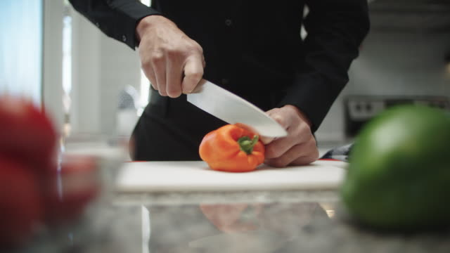 slow motion shot of a man es hands using a kitchen knife to slice through an orange bell pepper on a cutting board on a kitchen counter indoors - orangefarbige paprika stock-videos und b-roll-filmmaterial