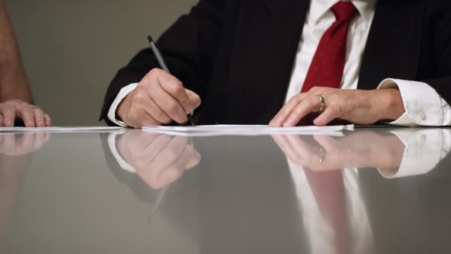 slow motion shot of a married, caucasian business man's hands signing documents at a conference table indoors - governo video stock e b–roll