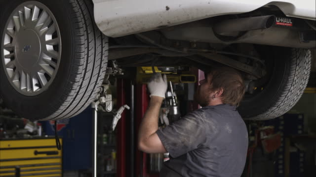 slow motion shot of a mechanic underneath a car. - laboratorio riparazioni video stock e b–roll