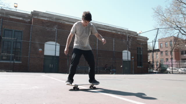 slow motion shot of a millennial skateboarding at a local school yard - 4k - t shirt stock videos & royalty-free footage