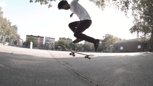 a slow motion shot of a mixed race man skateboarding through the streets of brooklyn - mixed race person stock videos & royalty-free footage