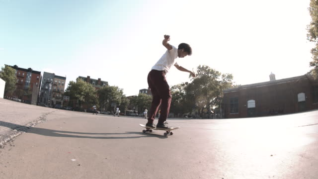 A slow motion shot of a mixed race man skateboarding through the streets of Brooklyn