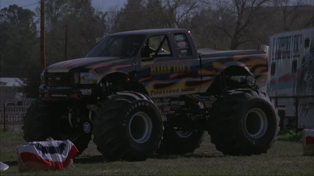 A slow motion shot of a monster truck crushing cars at a county fair.