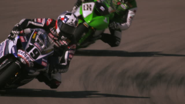stockvideo's en b-roll-footage met slow motion shot of a motorcycle racer maneuvering at a curve on a race track - motor