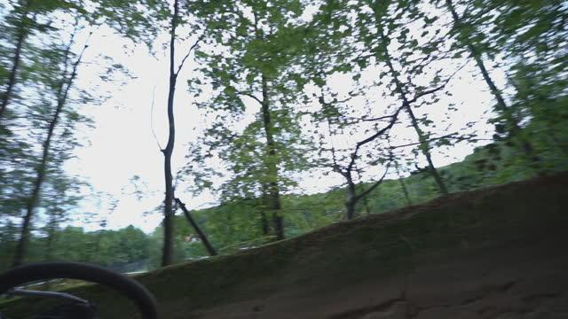 森の中の未舗装道路を降りるマウンテンバイカーのスローモーションショット - サイクリングロード点の映像素材/bロール