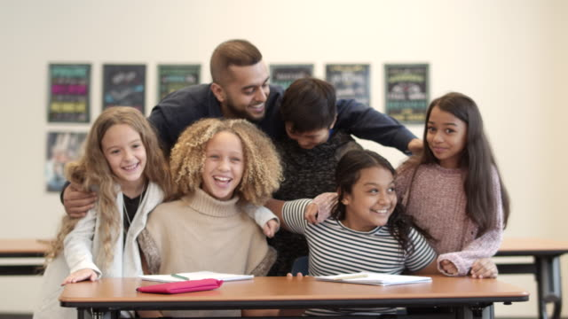 a slow motion shot of a multi-ethnic group of students laughing with their teacher - junior high stock videos & royalty-free footage