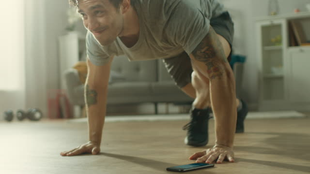 Slow Motion shot of a Muscular Fit Man in T-shirt and Shorts is Doing Mountain Climbers While Using a Stopwatch on His Phone. He is Training at Home in His Spacious and Bright Living Room with Minimalistic Interior.