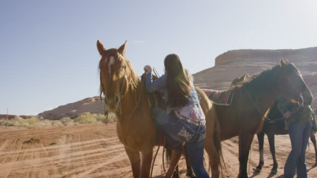 slow motion shot of a native american (navajo) girl in her teens stepping up on to a stirrup before mounting her horse on a bright, sunny day in the desert of arizona - native american reservation stock videos & royalty-free footage