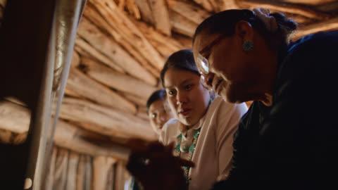 vídeos y material grabado en eventos de stock de disparo a cámara lenta de una abuela nativa americana (navajo) en sus sesenta enseñando a sus nietas adolescentes a tejer en un telar en el interior de un hogan (navajo hut) - culturas