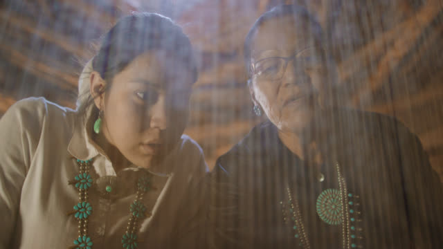 slow motion shot of a native american grandmother (navajo) in her sixties teaching her teenaged granddaughter how to weave at a loom indoors in a hogan (navajo hut) - navajo culture stock videos & royalty-free footage