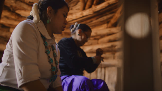 vidéos et rushes de slow motion shot of a native american grandmother in her sixties preparing to weave at her loom while her teenaged granddaughter watches indoors in a hogan (navajo hut) - métier à tisser