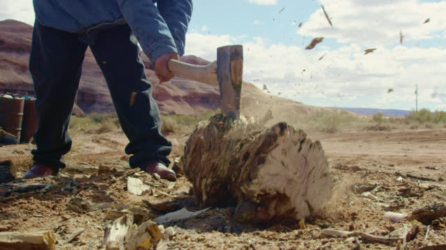 slow motion shot of a native american teenaged boy using an axe to chop firewood in monument valley in arizona/utah on a clear, sunny day with a large rock formation behind him - firewood stock videos & royalty-free footage