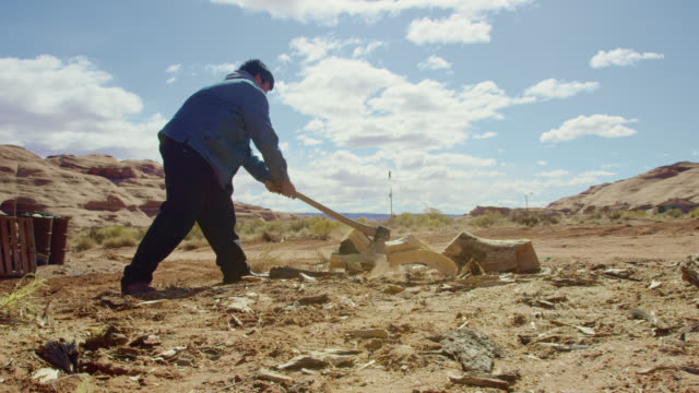 slow motion shot of a native american teenaged boy (navajo) using an axe to chop firewood in monument valley in arizona/utah on a clear, sunny day with a large rock formation behind him - lumberjack stock videos & royalty-free footage