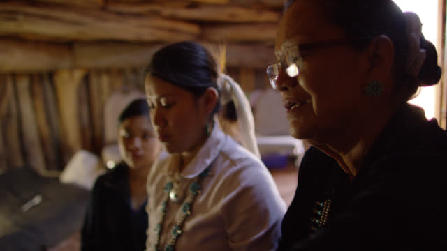 slow motion shot of a native american teenaged girl weaving at a loom while her navajo grandmother in her sixties instructs her and her teenaged sister watches indoors in a hogan (navajo hut) - north american tribal culture stock videos & royalty-free footage