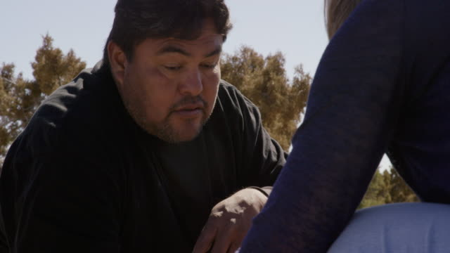 slow motion shot of a navajo man in his forties crouching and talking with a caucasian woman/customer who points to some native american-style jewelry he is selling on a sunny day outdoors - indigenous peoples of the americas stock videos & royalty-free footage