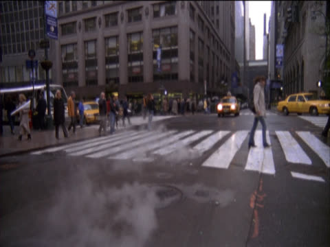 Slow Motion Shot of a Pedestrian Crossing, Steam Rising From a Manhole and Yellow Cabs on 5th Avenue, New York, USA