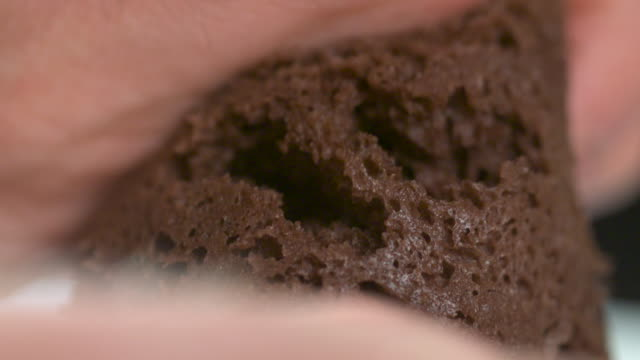 Slow motion shot of a person breaking apart a piece of chocolate cake.