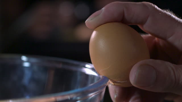 Slow motion shot of a person cracking an egg against the side of a glass bowl.