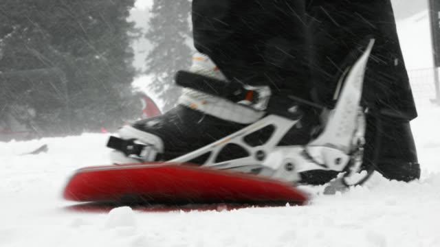 vídeos de stock e filmes b-roll de slow motion shot of a person throwing his or her snowboard on to snow, putting their booted foot into the bindings, clipping the bindings, and snowboarding away at eldora ski resort near boulder, colorado on a snowy, overcast day in winter - snowboard