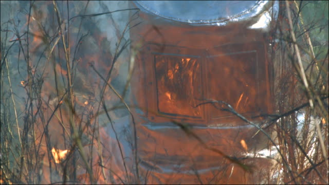 Slow motion shot of a person walking through a bush fire while wearing a fire protection suit.