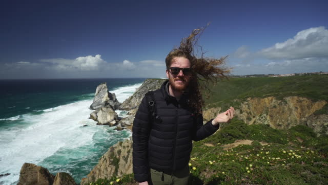 slow motion shot of a photographer standing on a windy cliff near the ocean - long stock videos & royalty-free footage