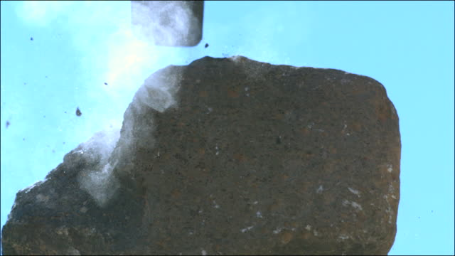 Slow motion shot of a piece of limestone being hit with a sledgehammer.