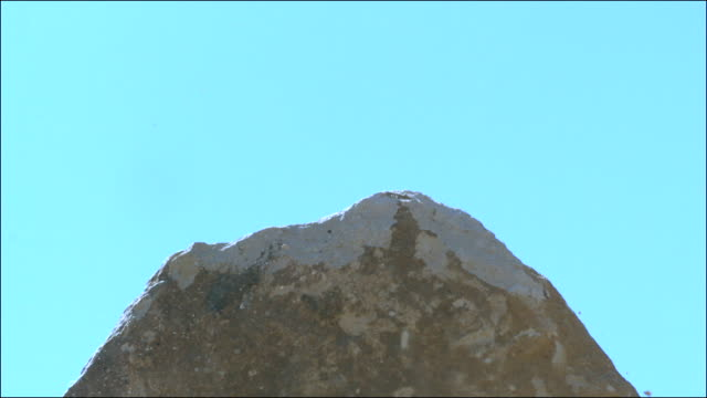 Slow motion shot of a piece of limestone being struck by a sledge hammer.