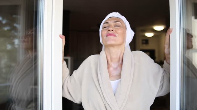 slow motion shot of a pretty old woman opening the balcony door and enjoying the fresh sunny morning - bathrobe stock videos & royalty-free footage