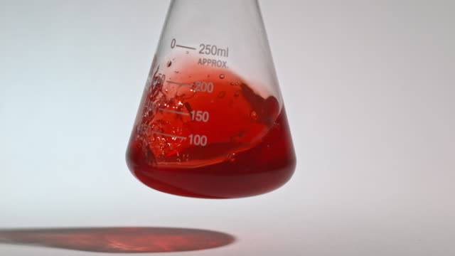 vídeos y material grabado en eventos de stock de slow motion shot of a red liquid being swirled inside a laboratory glass flask. - laboratorio