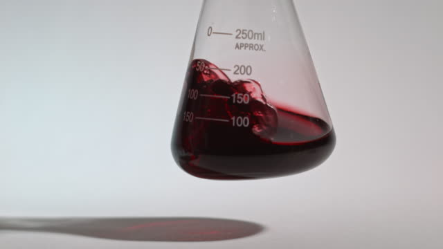 slow motion shot of a red liquid being swirled inside a laboratory glass flask. - measuring stock videos & royalty-free footage