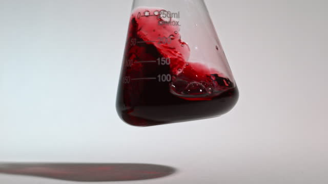 slow motion shot of a red liquid being swirled inside a laboratory glass flask. - laboratory flask stock videos & royalty-free footage