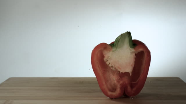 slow motion shot of a red pepper falling onto a wooden block. - peperone dolce video stock e b–roll