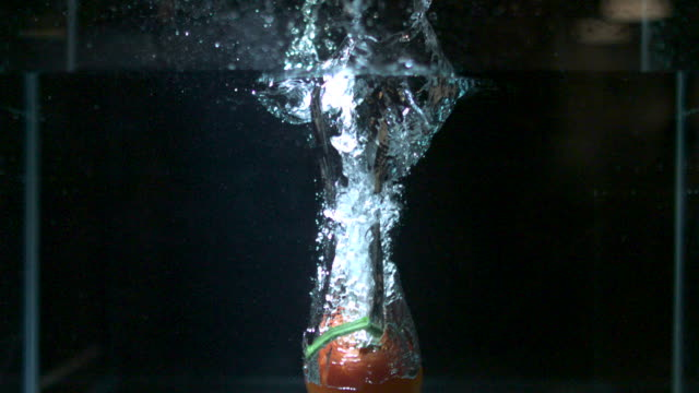 Slow motion shot of a red tomato being dropped into a tank of water.