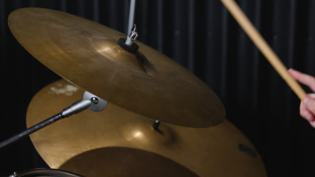 Slow motion shot of a ride cymbal being repeatedly hit on a drum kit