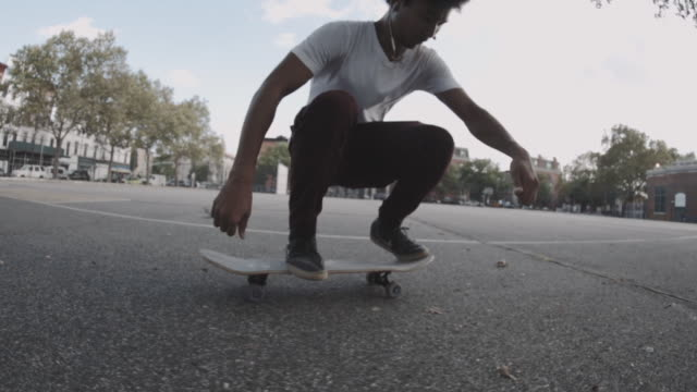 slow motion shot of a skateboarder crashing on the streets of brooklyn - 柵点の映像素材/bロール