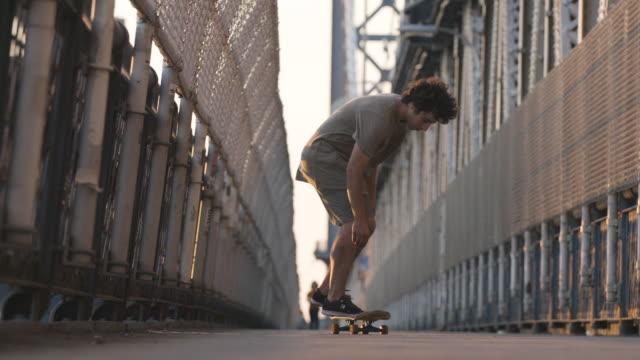 vídeos de stock e filmes b-roll de slow motion shot of a skateboarder crossing new york city's manhattan bridge - caminho adiante