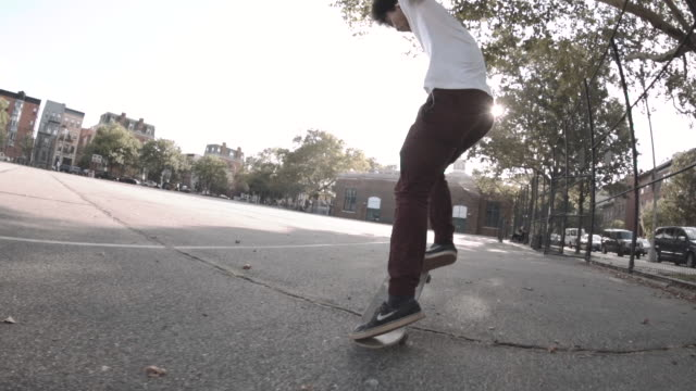 a slow motion shot of a skateboarder falling on the streets of new york city - 柵点の映像素材/bロール