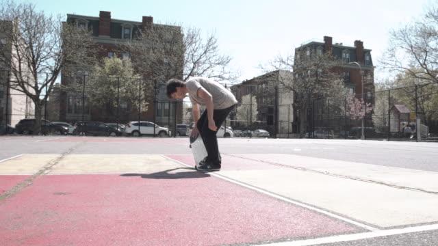 slow motion shot of a skateboarder in the streets of brooklyn, nyc - auf einem bein stock-videos und b-roll-filmmaterial